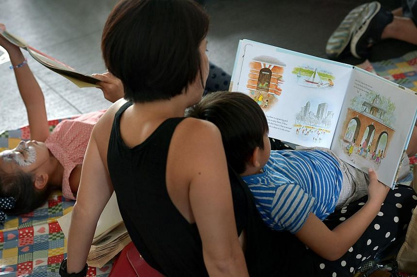 A mother reading And Tango Makes Three during the Let's Read Together event on July 13. The event was held in response to the NLB's decision to pulp three children's books featuring same-sex parents and attracted 400 people, including children.