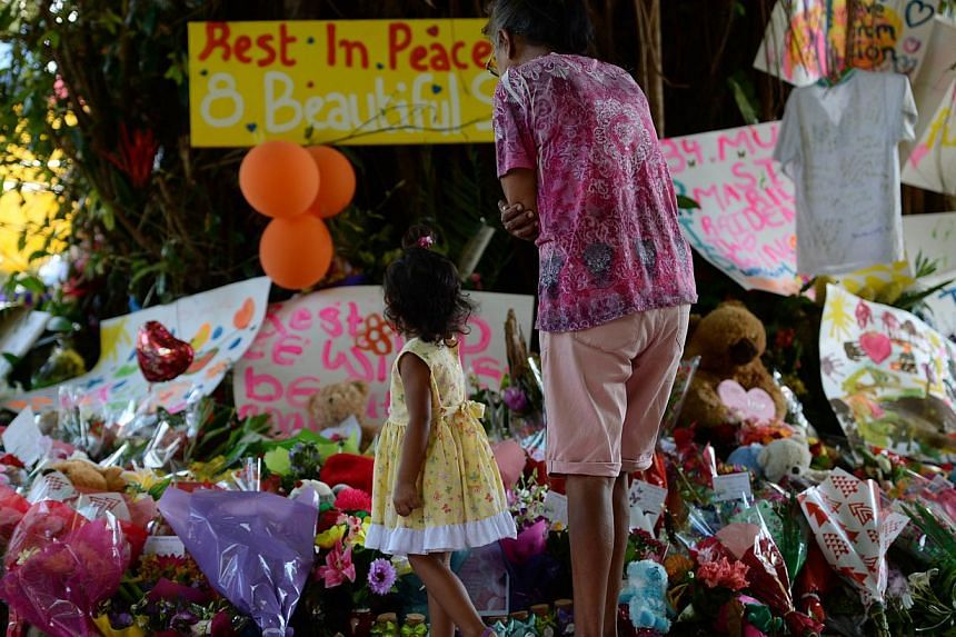 Mourners at the scene where eight children ranging from babies to teenagers were found dead in a house in the northern Australian city of Cairns. TheAustralian mother charged with killing the eight children will have her case heard in January,