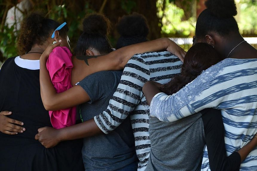 This photo taken on Dec 20, 2014 shows people hugging at the scene where eight children ranging from babies to teenagers were found dead in a house in the northern Australian city of Cairns. -- PHOTO: AFP