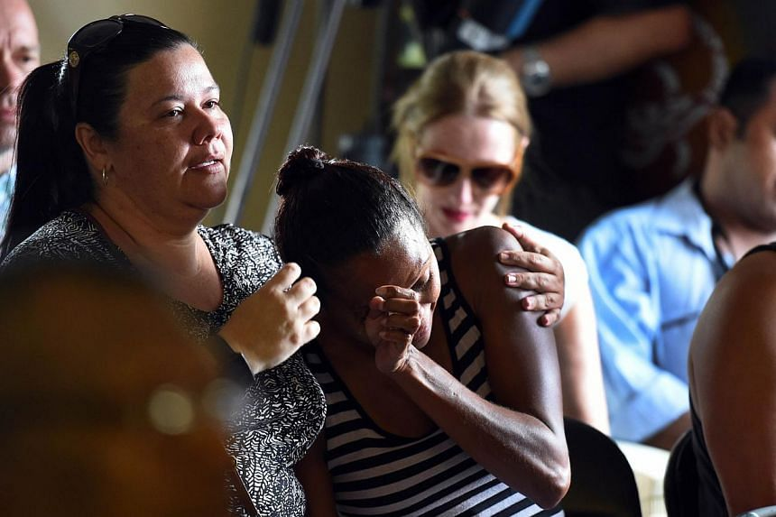 People attend a church service to remember eight children who were killed by their mother in the Cairns suburb of Manoora, on Dec 21, 2014. -- PHOTO: AFP