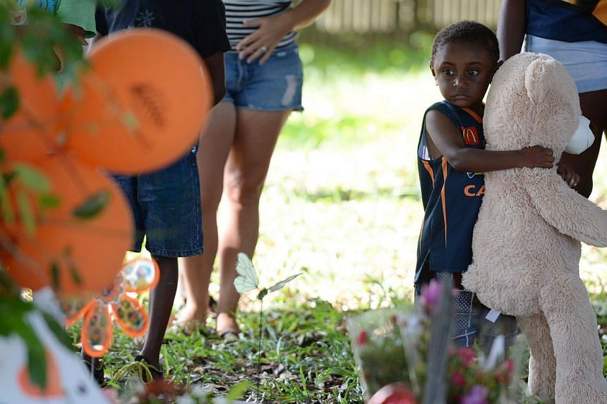 This photo taken on Dec 20, 2014 shows a local boy holding a large teddy bear at the scene where eight children ranging from babies to teenagers were found dead in a house in the northern Australian city of Cairns. -- PHOTO: AFP