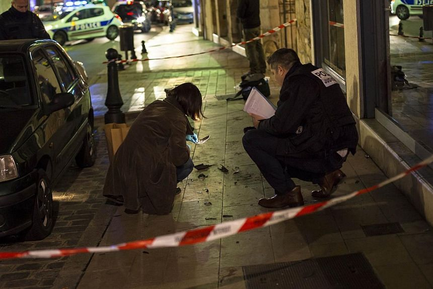 """Policemen collect evidence on Dec 21, 2014 in Dijon on the site where a driver shouting """"Allahu Akbar"""" (God is great) ploughed into a crowd injuring 11 people, two seriously, a source close to the investigation said. -- PHOTO: AFP"""