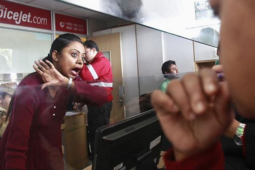 An employee of SpiceJet Airlines speaks with a passenger at the ticket counter at an airport on the outskirts of Agartala, capital of India's northeastern state of Tripura on Dec 17, 2014. -- PHOTO: REUTERS