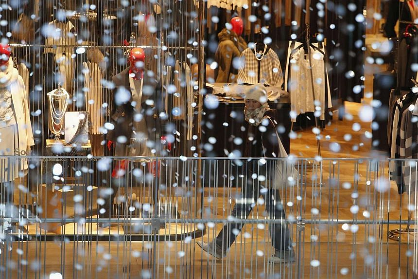 A woman walks past a shop window at a department store in Tokyo on Dec 19, 2014. -- PHOTO: REUTERS