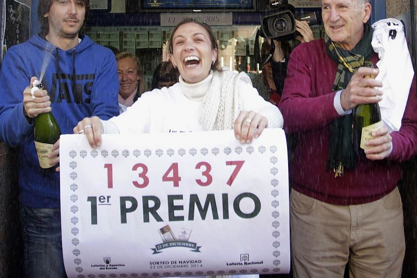 Lottery seller Raquel Carrasco (centre) holds a sign with the winning number of Spain's Christmas Lottery, El Gordo, in La Eliana near Valencia on Dec 22, 2014. -- PHOTO: REUTERS