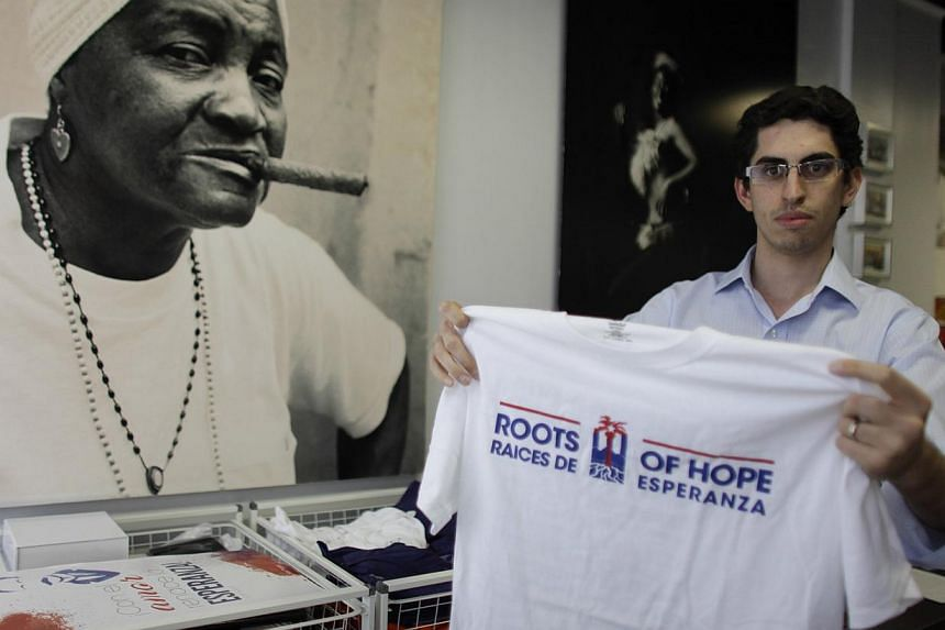 """Raul Moas holds a T-shirt of his organisation """"Roots of Hope"""" in Miami Beach, Florida ove the weekend. The Obama Administration's new policy on Cuba is banking on a groundswell of support from new voices in Miami, the young Cuban professionals who do"""