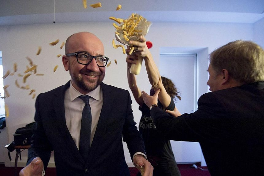 Pierre Rion (right) tries to intervene as activists throw fries and mayonnaise on Belgian Prime Minister Charles Michel, a protest action of feminist activists LilithS (formerly the Belgian branch of Femen), at a conference at the Cercle de Wal