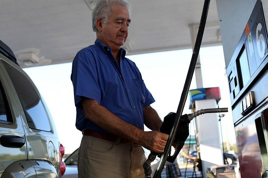 A customer puts petrol into a vehicle at the U-gas station in Miami, Florida earlier this month. -- PHOTO: AFP