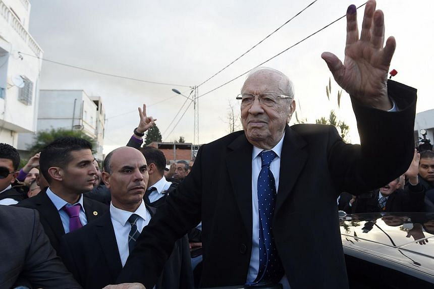 Tunisian presidential candidate for the anti-Islamist Nidaa Tounes party, Beji Caid Essebsi waves to supporters after placing his vote on Dec 21, 2014 in Tunis. -- PHOTO: AFP