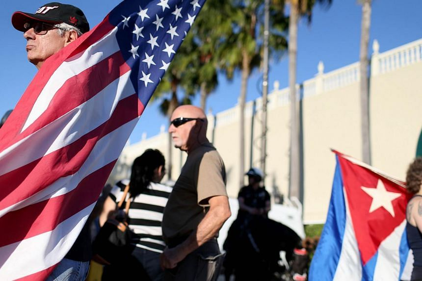 People stand outside the Little Havana restaurant Versailles after news that US contractor Alan Gross was released from a Cuban prison and US President Barack Obama's announcement on United States-Cuba policy change on Dec 17, 2014 in Miami, Florida.