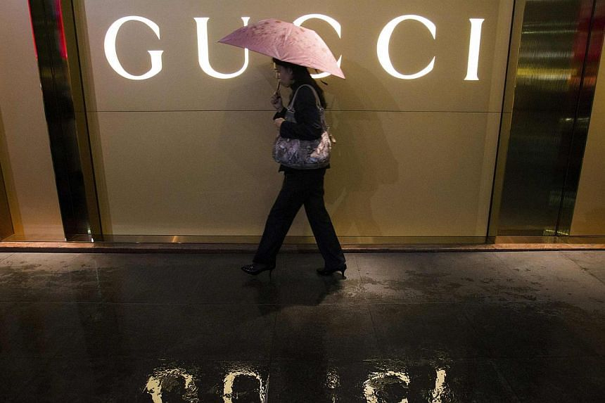 A woman holding an umbrella walks past a company logo of a Gucci boutique outside a shopping mall in central Guangzhou. The Italian fashion house said it would strengthen controls on its suppliers after a television programme showed Chinese employees