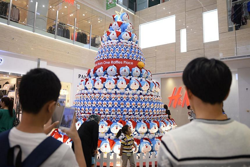 People take pictures in front of the Doraemon Tree at One Raffles Place on Dec 22, 2014. -- ST PHOTO: MARK CHEONG