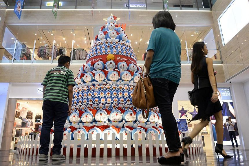 People pass by the Doraemon Tree at One Raffles Place on Dec 22, 2014. -- ST PHOTO: MARK CHEONG
