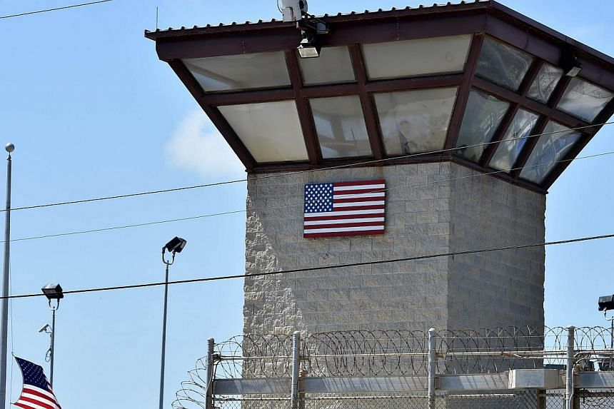 """This April 8, 2014 file photo made during an escorted visit and reviewed by the US military shows the razor wire-topped fence and the watch tower of """"Camp 6"""" detention facility at the US Naval Station in Guantanamo Bay, Cuba.The US official res"""