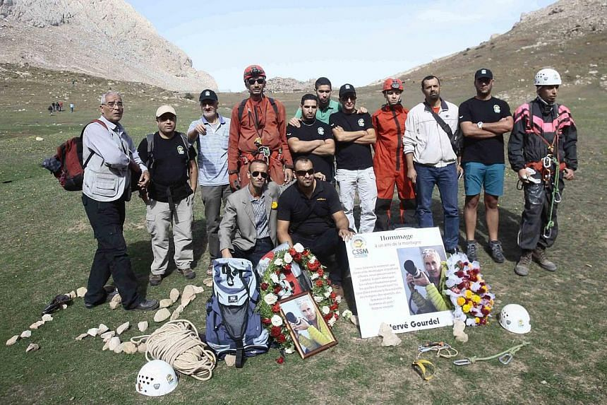 Residents and mountain climbers pose as they pay their respects to mountain guide Frenchman Herve Gourdel, who was beheaded by a militant group, at the Tikjda mountain ranges near the village of Ait Ouabane on Oct 10, 2014. -- PHOTO: REUTERS