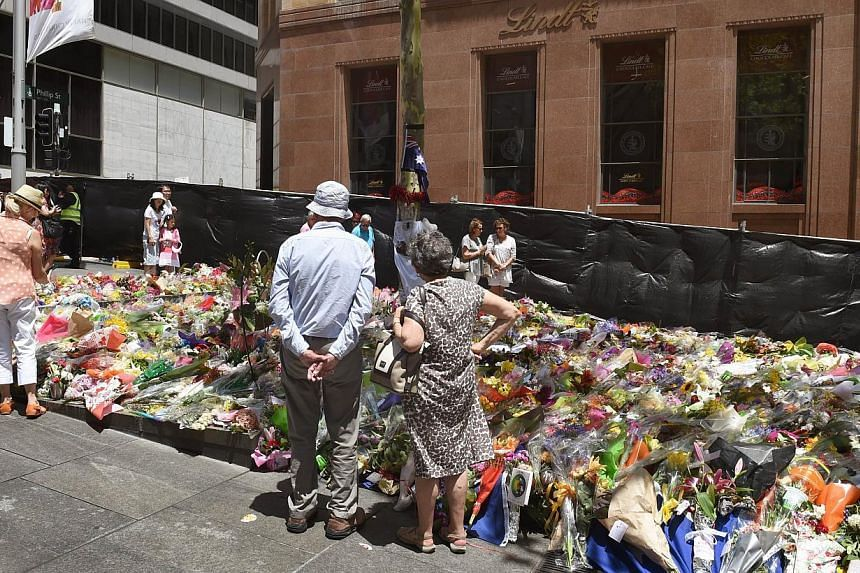People look at the floral tributes left outside the Lindt cafe (rear) in Sydney's Martin Place, one week after a siege at the cafe which saw two hostages and the gunman killed on Dec 22, 2014. -- PHOTO: AFP