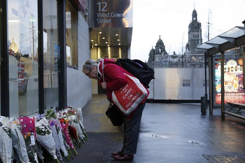 A woman looks at flowers close to the scene where a refuse truck crashed into pedestrians in George Square, Glasgow, Scotland on Dec 23, 2014. -- PHOTO: REUTERS