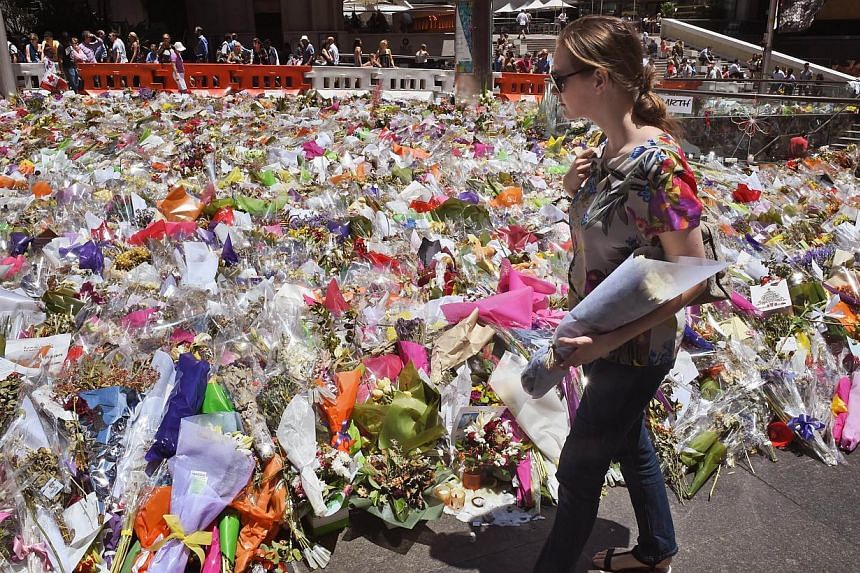 A woman arrives with a bouquet for the floral tributes left in Sydney's Martin Place, one week after a siege at the Lindt cafe which saw two hostages and the gunman killed, on Dec 22, 2014. -- PHOTO: AFP