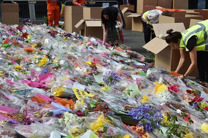 Flowers being removed at a memorial site outside the Lindt cafe in Sydney on Dec 23, 2014, one week after a siege at the cafe which saw two hostages Katrina Dawson and Tori Johnson along with the gunman killed. -- PHOTO: AFP