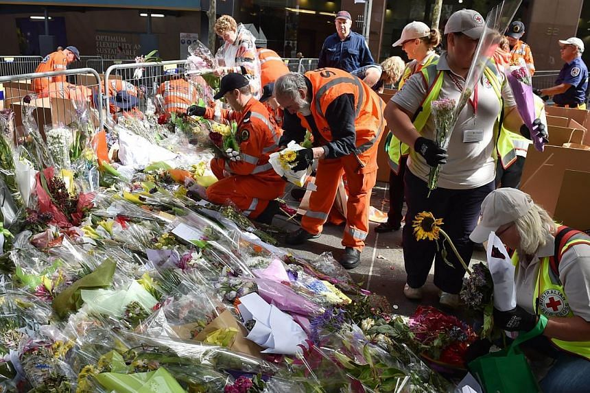 Volunteers removing flowers at a memorial site outside the Lindt cafe in Sydney on Dec 23, 2014, one week after a siege at the cafe which saw two hostages Katrina Dawson and Tori Johnson along with the gunman killed. -- PHOTO: AFP