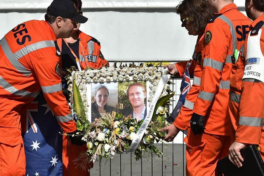 Volunteers removing a framed photograph of Katrina Dawson (left) and Tori Johnson (right) outside the Lindt cafe in Sydney on Dec 23, 2014, one week after a siege at the cafe which saw the two hostages and the gunman killed. -- PHOTO: AFP