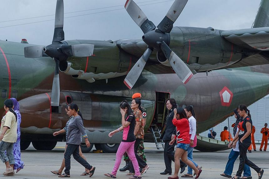Undocumented Indonesian workers walking on the tarmac towards an Indonesian military C-130 aircraft at Subang Air Force base in Subang, outside Kuala Lumpur, on Dec 23, 2014. -- PHOTO:AFP