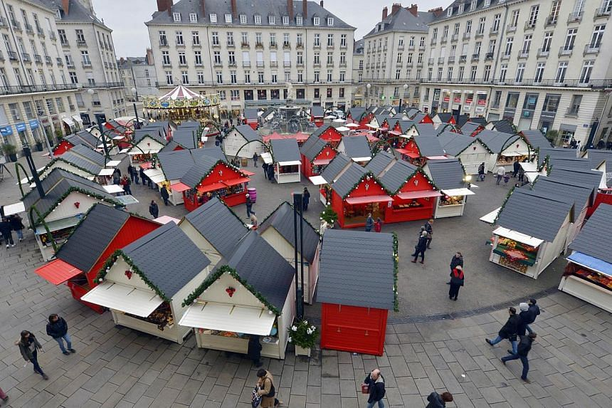 People visit the Christmas market in the western French city of Nantes on Dec 23, 2014, a day after a man rammed into shoppers with his car. -- PHOTO: AFP