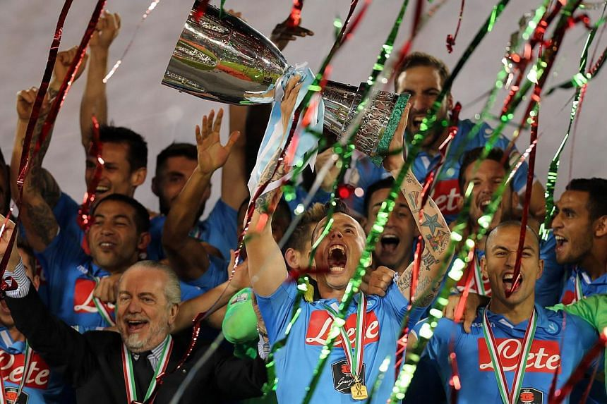 Napoli's Slovak midfielder and captain Marek Hamsik lifting the Italian Super Cup trophy after defeating Serie A champions Juventus at the Sheikh Jassim Bin Hamad Stadium in the Qatari capital Doha on Dec 22, 2014. -- PHOTO: AFP