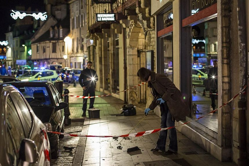 """A policewoman collects evidence on Sunday in Dijon on the site where a driver shouting """"Allahu Akbar"""" (""""God is great"""") ploughed into a crowd injuring 11 people, two seriously, a source close to the investigation said. -- PHOTO: AFP"""