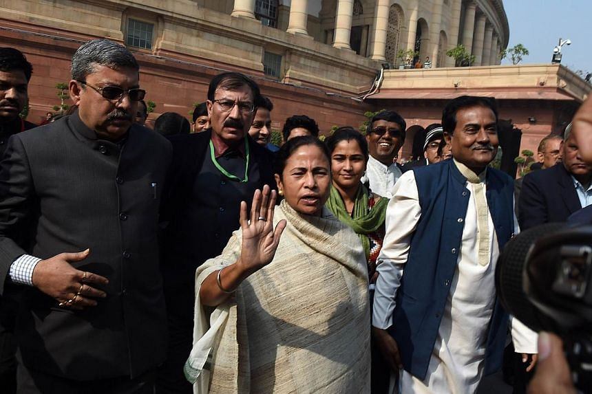 West Bengal Chief Minster and Trinamool Congress (TMC) President Mamta Banerjee (centre) interacts with the media outside Parliament in New Delhi. The Indian parliament winter session ended on Tuesday. -- PHOTO: AFP