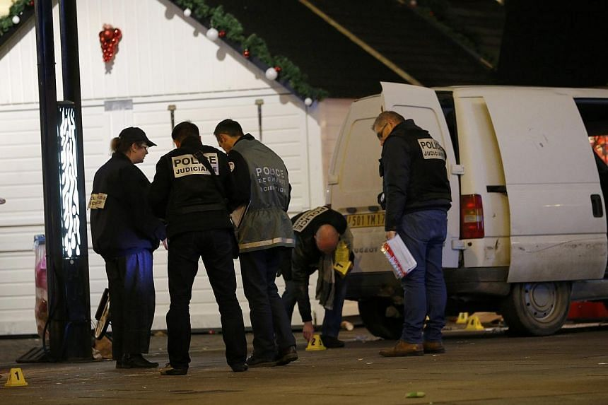 French police investigators work near a van which was driven into a crowd, injuring ten people, including five seriously wounded, according to French media, in Nantes on Monday. Five people including the driver suffered serious injuries and one of th
