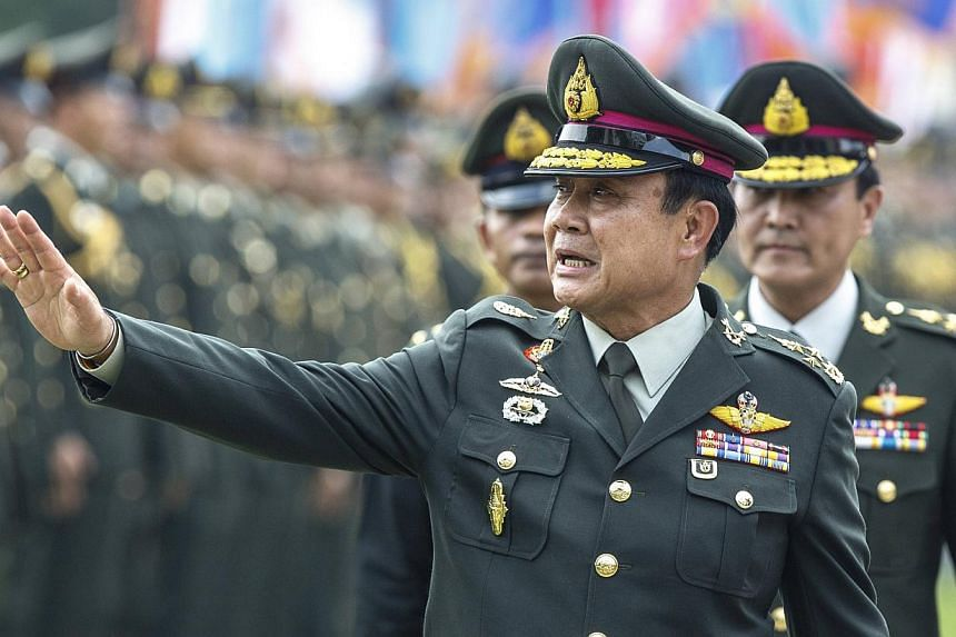 Thailand's Prime Minister Prayuth Chan-ocha (pictured) waves after a handover ceremony for the new Royal Thai Army Chief, General Udomdej Sitabutr, at the Thai Army Headquarters in Bangkok on Sept 30, 2014. A general election to return Thailand to de