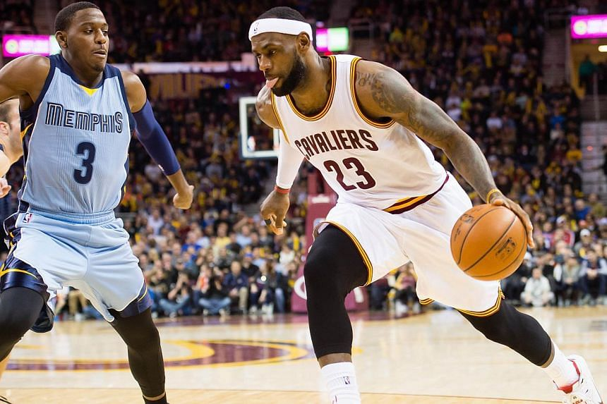 LeBron James (right) of the Cleveland Cavaliers drives past Jordan Adams of the Memphis Grizzlies during the second half at Quicken Loans Arena on Dec 21, 2014 in Cleveland, Ohio. -- PHOTO: AFP