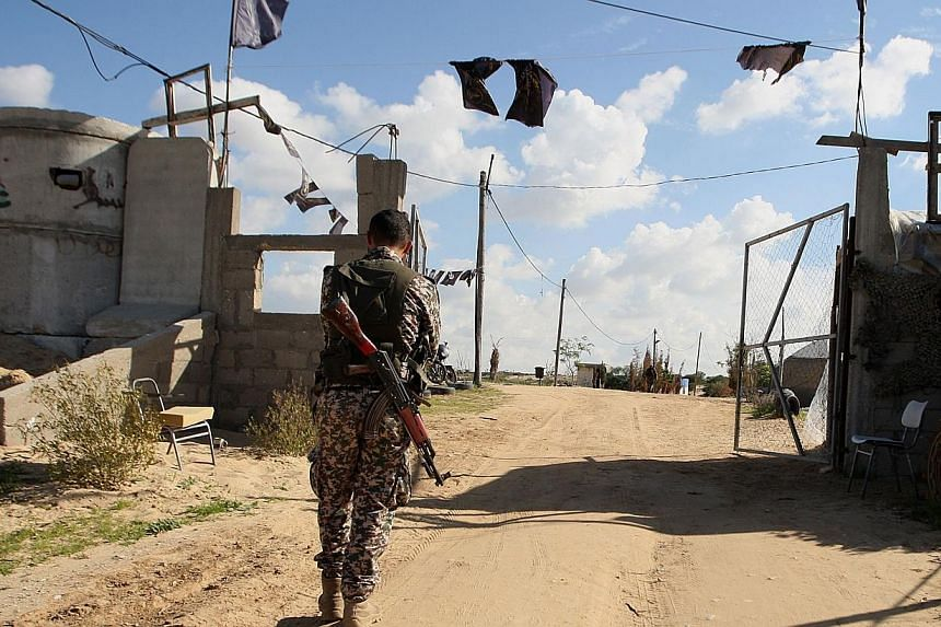 A Palestinian militant from the Islamic Jihad armed wing, the Al-Quds Brigades, walks near a military post on Dec 20, 2014 in Khan Yunis, in the southern Gaza Strip.Israeli warplanes hit southern Gaza Wednesday after sniper fire against troops,