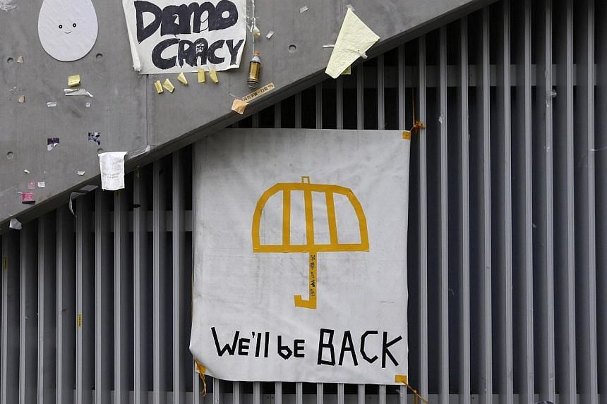 """A poster of an umbrella with the words """"We'll be back"""" written underneath is pictured on a wall at the main """"Occupy"""" protest site at Admiralty in Hong Kong on Dec 11, 2014.Hong Kong's pro-democracy protest camps may have been swept away but one"""