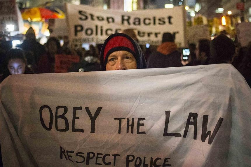 A man holds a banner in front of protesters, demonstrating decisions by grand juries in New York and Missouri not to indict white police officers in the killings of unarmed black men, as they marched down Fifth Avenue in Manhattan, New York on Dec 23