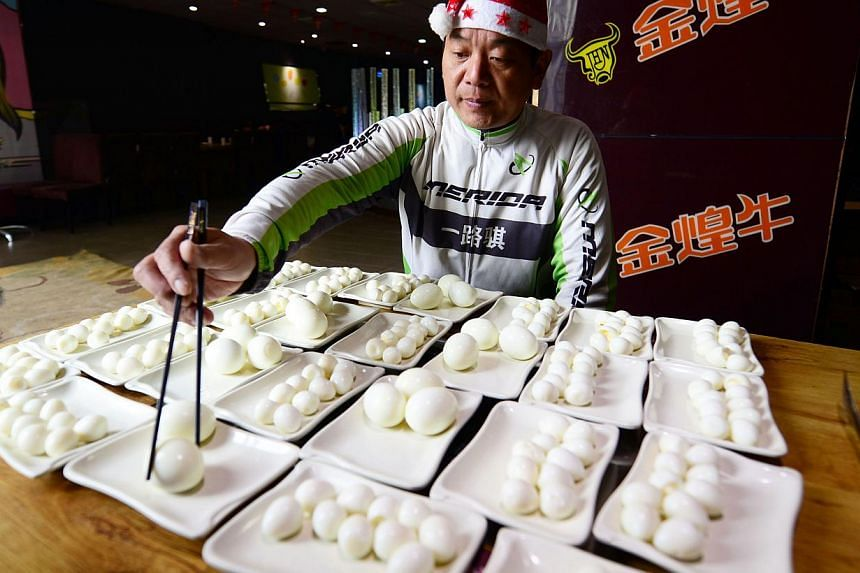 Chinese competitive eater Pan Yizhong picking up an egg at a buffet restaurant in Changsha, in central China's Hunan province on Dec 23, 2014. -- PHOTO: AFP