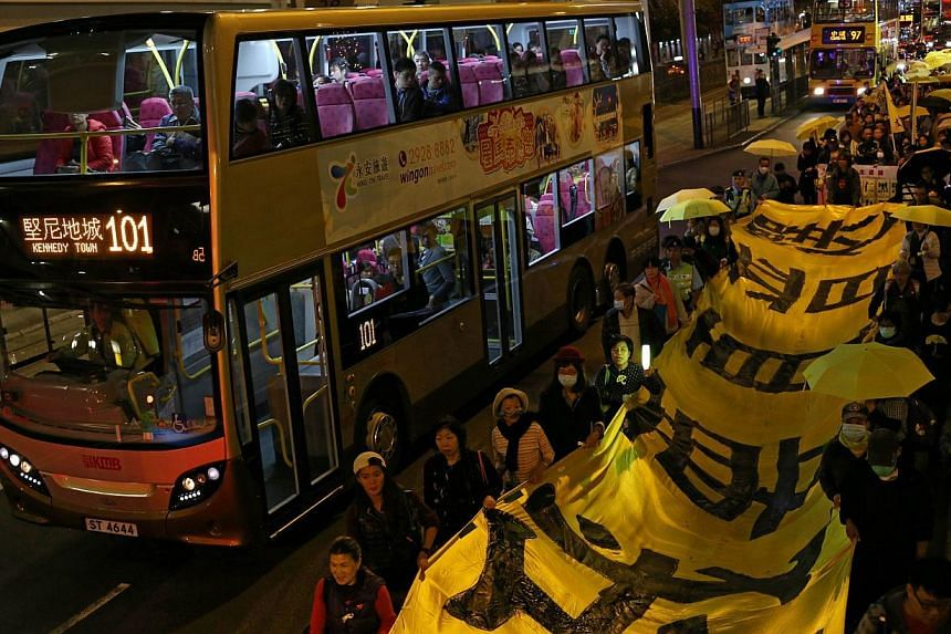"""Protesters carry a long banner, with the words """"I want real universal suffrage"""" in Chinese, and yellow umbrellas -- the recent symbol of Hong Kong's democracy movement -- during a march to mark Christmas Eve on Dec 24, 2014.Around 100 pro-democ"""