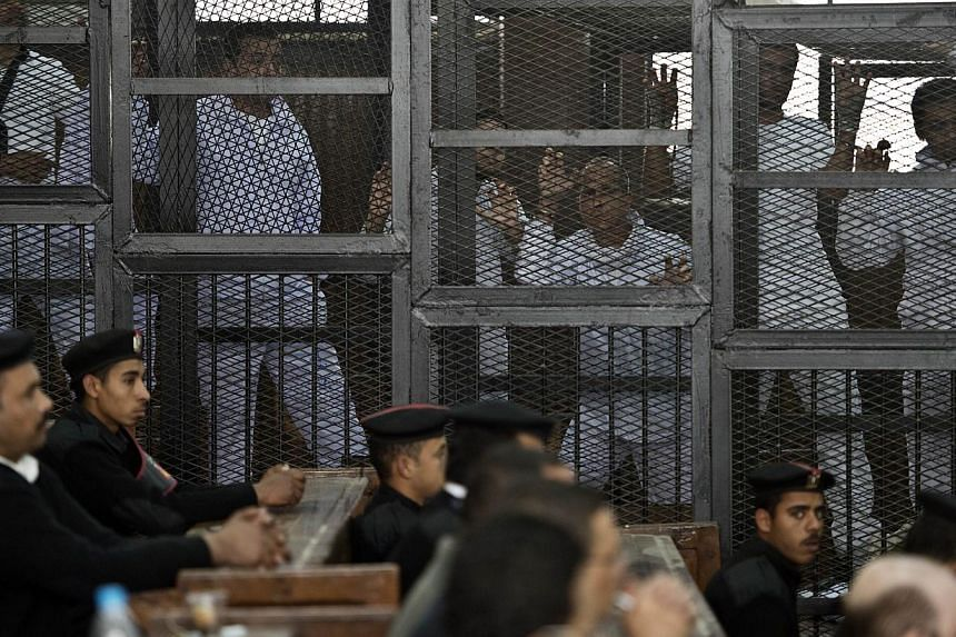 Australian journalist Peter Greste (3rd right) of Al-Jazeera and his colleagues stand inside the defendants cage during their trial for allegedly supporting the Muslim Brotherhood at Cairo's Tora prison on March 5, 2014. -- PHOTO: AFP