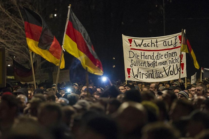 """A picture taken on Dec 15, 2014, shows supporters of the PEGIDA movement, """"Patriotische Europaeer gegen die Islamisierung des Abendlandes,"""" which translates to """"Patriotic Europeans Against the Islamification of the Occident,"""" taking part in a r"""
