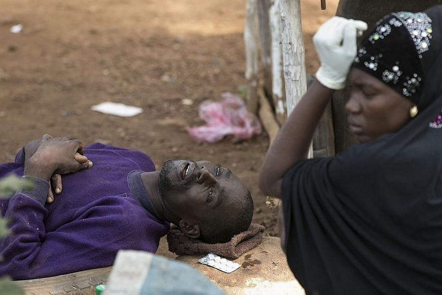 Adama Tarawallie reacts near her husband Ibrahim, 31, a suspected Ebola victim, as they wait to be transported from Devils Hole North, west of Freetown, Sierra Leone, in this Dec 17, 2014, file photo.The Ebola crisis in West Africa that claimed
