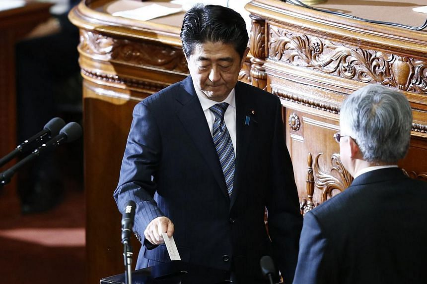 Japan's Prime Minister Shinzo Abe casts a vote at the Lower House of the Parliament in Tokyo on Dec 24, 2014. -- PHOTO: REUTERS