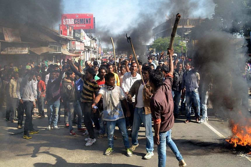Activists of the Assam Tea Tribes Student Association (ATTSA) shout slogans as they block the road with burning tyres during a protest against attacks on villagers by militants in four different locations, at Biswanath Chariali in the Sonitpur distri