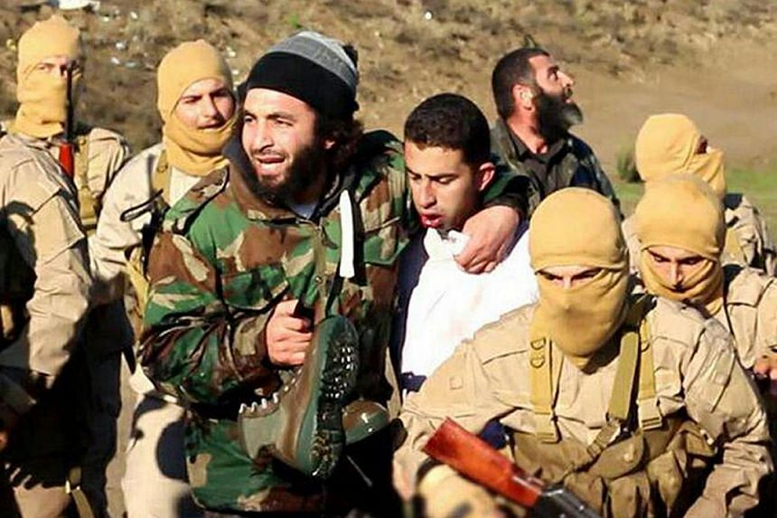 A still image released by the Islamic State group's branch in Raqa on militant websites on Dec 24, 2014, purportedly shows a Jordanian pilot (centre) captured by ISIS fighters. -- PHOTO: AFP