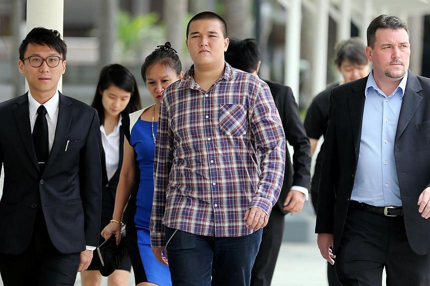 David William Graaskov (center) and his parents and lawyers arriving at the State Courts. The teenager is accused of conspiring with four others to commit vandalism at the rooftop of a HDB block in Toa Payoh on May 7, 2014. He also removed a reflecti