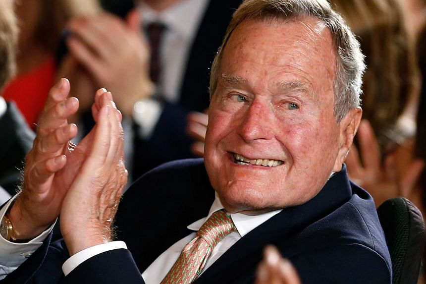 Former President George H. W. Bush applauds during an event to honor the winner of the 5,000th Daily Point of Light Award at the White House in Washington in this July 15, 2013 file image. -- PHOTO: REUTERS