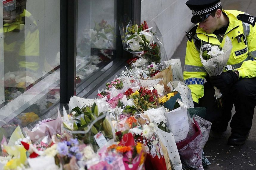 A police officer places flowers from a member of the public near the scene where a refuse truck crashed into pedestrians in George Square, Glasgow, Scotland Dec 23, 2014. -- PHOTO: REUTERS