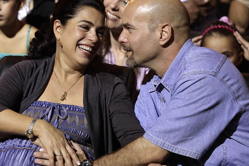 """Gerardo Hernandez , one of the so-called """"Cuban Five"""", reacts with his wife Adriana Perez (right) during Cuban musician Silvio Rodriguez's concert in Havana Dec 20, 2014.Officials have confirmed that a US senator helped a Cuban spy imprisoned i"""