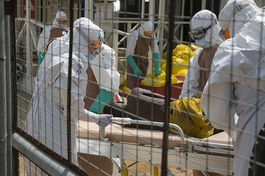 Health workers lift a newly admitted Ebola patient onto a wheeled stretcher in the Kerry town Ebola treatment centre outside Freetownon Dec 22, 2014. -- PHOTO: REUTERS