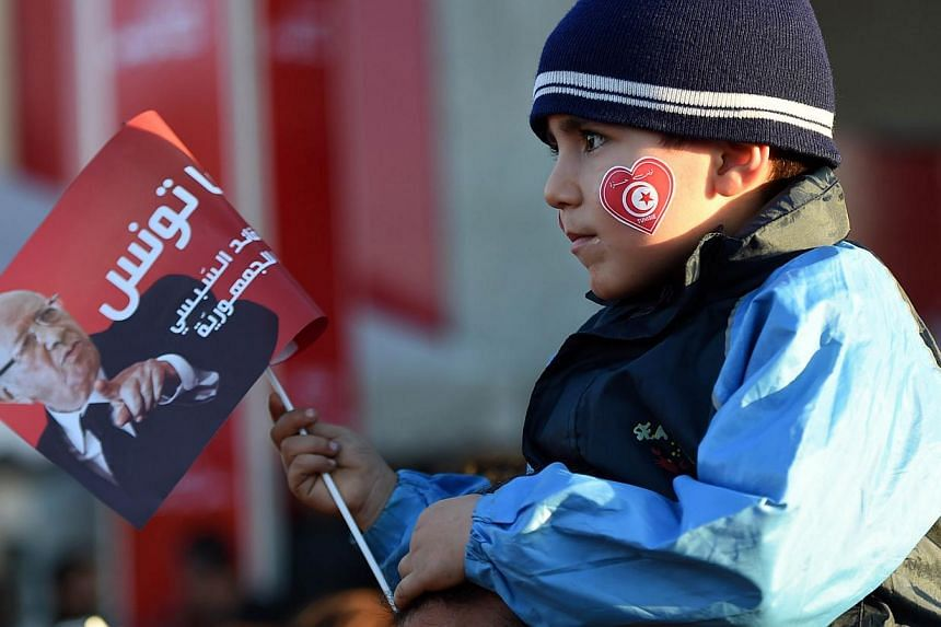 A child holds a flyer as supporters of Tunisian newly-elected President Beji Caid Essebsi celebrate after his victory on Dec 22, 2014 in Tunis. Tunisia's new leader Beji Caid Essebsi said the country has turned the page on dictatorship after a p